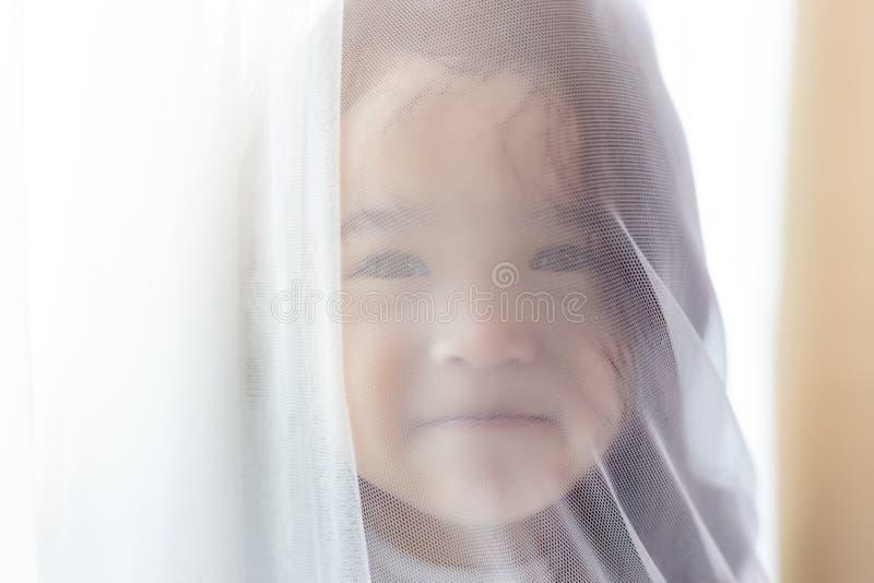 Menina bonito pequena do retrato Criança pequena bonita atrativa que esconde atrás da cortina na casa A criança do berçário olha  fotos de stock