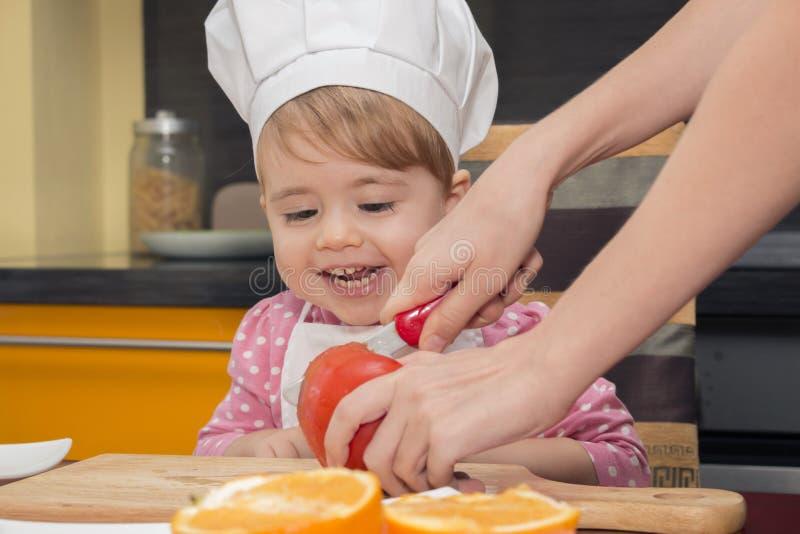 Menina bonito pequena do sorriso no terno do cozinheiro chefe que joga na cozinha A faca da mamã corta um tomate imagem de stock royalty free