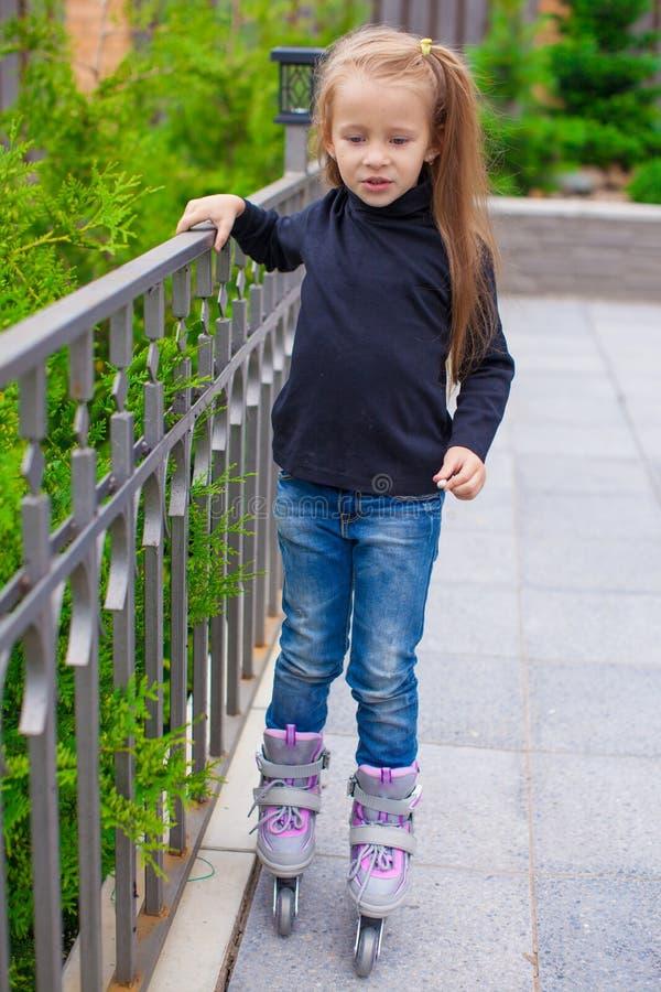 Menina bonito pequena em patins de rolo na frente dela fotos de stock royalty free