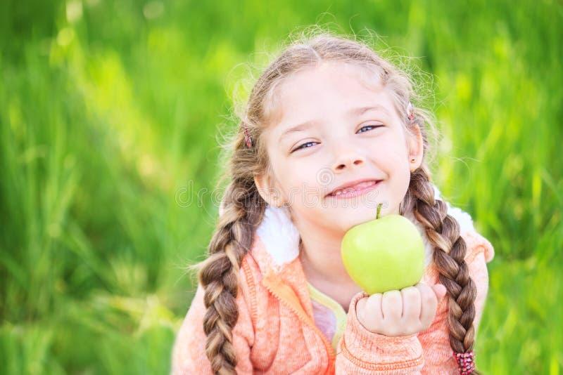 Menina bonito pequena em um fundo da grama verde com uma maçã imagem de stock royalty free