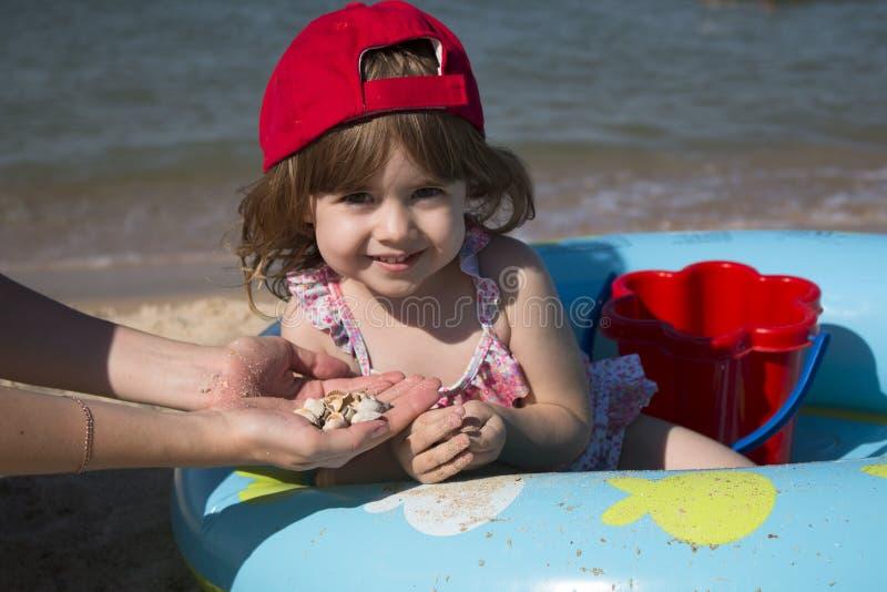 A menina bonito pequena em um tampão vermelho senta-se em uma associação e em jogos do ` s das crianças com sua mãe nas conchas d fotos de stock