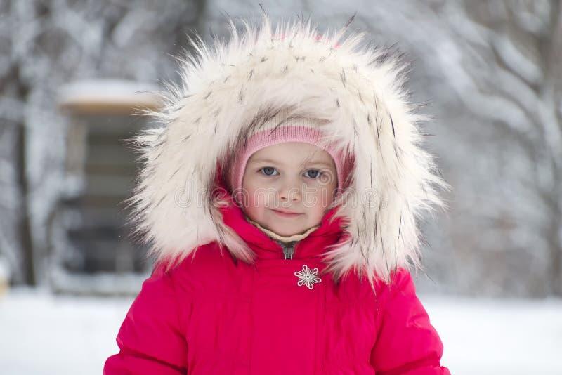 Menina bonito pequena em uma capa grande da pele no inverno fotografia de stock royalty free