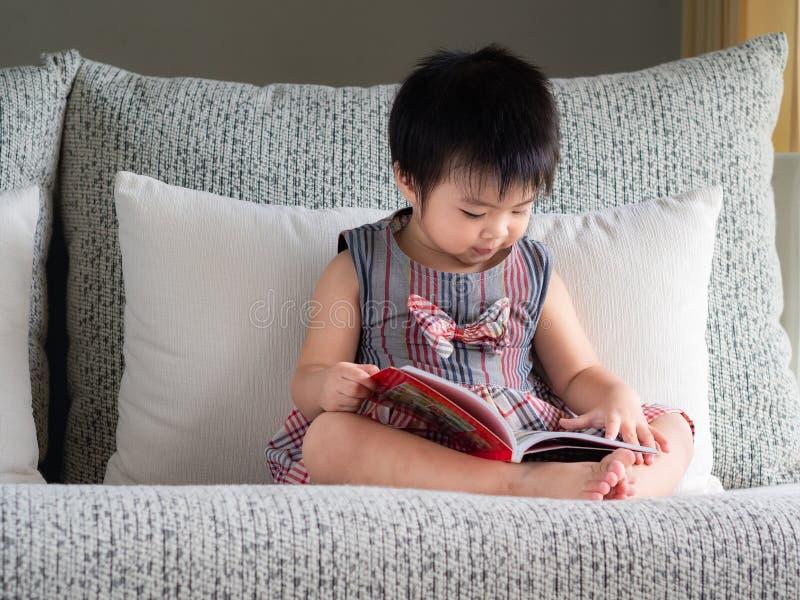 A menina bonito pequena feliz está lendo o livro no sofá branco Ed imagens de stock royalty free