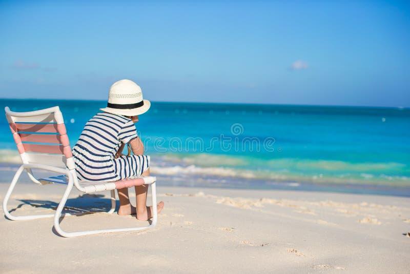 A menina bonito pequena na cadeira de praia relaxa nas Caraíbas fotografia de stock