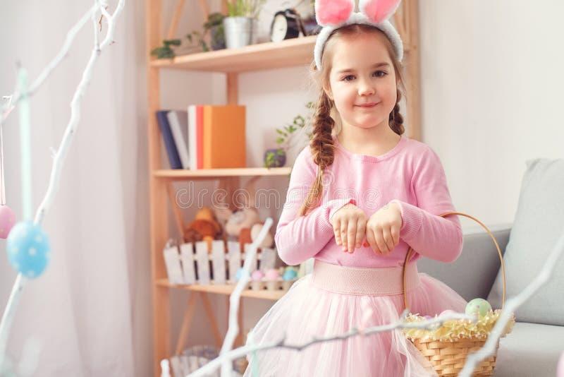 Menina bonito pequena no conceito da celebração de easter das orelhas e do vestido do coelho em casa que guarda a cesta com ovos imagem de stock