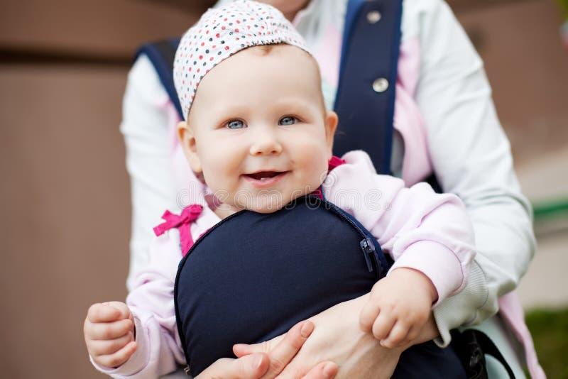 Menina bonito pequena no estilingue. imagem de stock