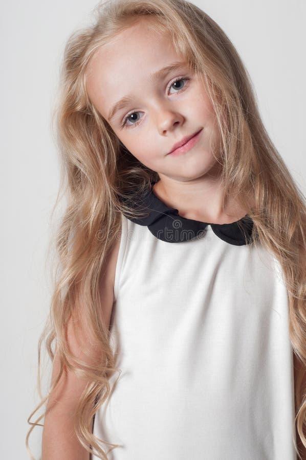 Menina bonito pequena no vestido branco fotos de stock