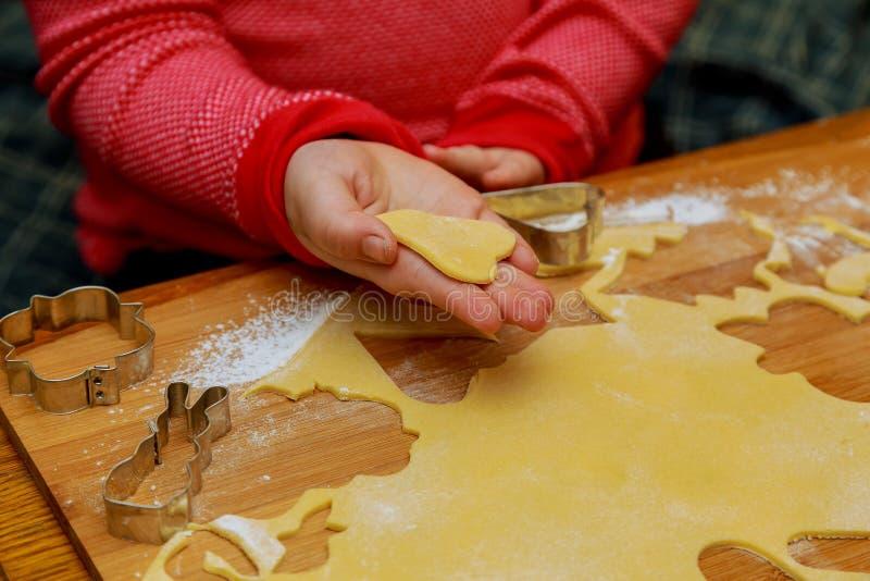 A menina bonito pequena põe cookies sobre de cozimento fotos de stock royalty free