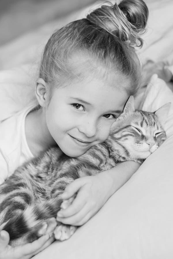 Menina bonito pequena que abraça afetuosamente o gatinho imagem de stock royalty free