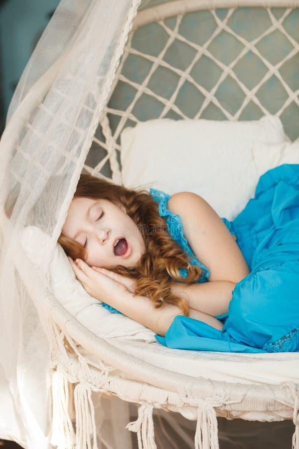Menina bonito pequena que dorme no balanço imagem de stock