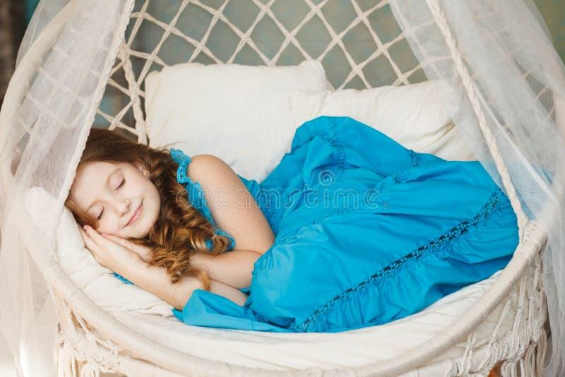 Menina bonito pequena que dorme no balanço imagens de stock
