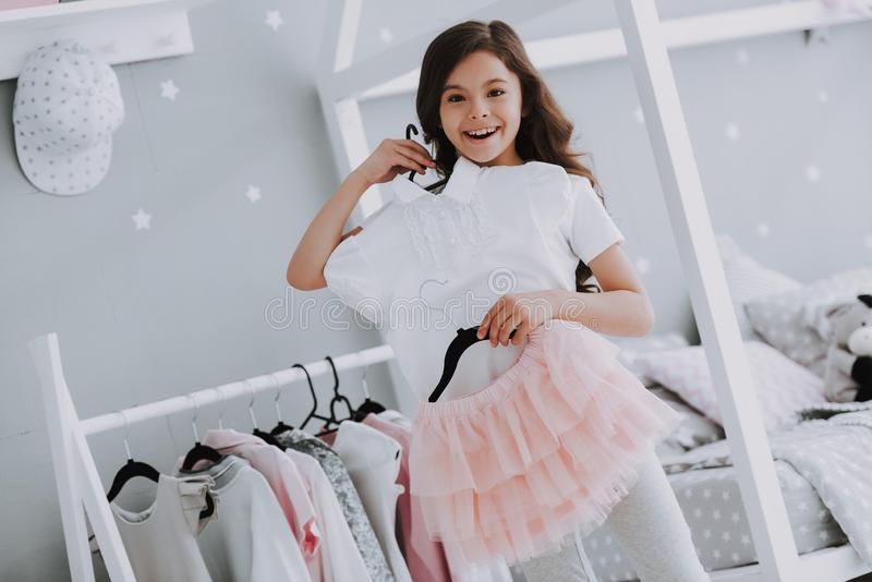 Menina bonito pequena que escolhe um vestido no quarto fotografia de stock royalty free