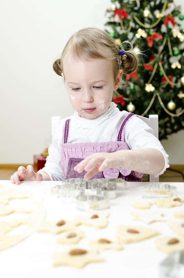 Menina bonito pequena que faz bolinhos imagens de stock royalty free