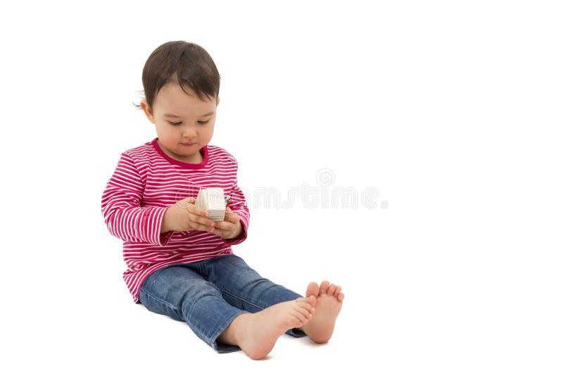 Menina bonito pequena que guarda uma caixa de presente, isolada no branco fotografia de stock