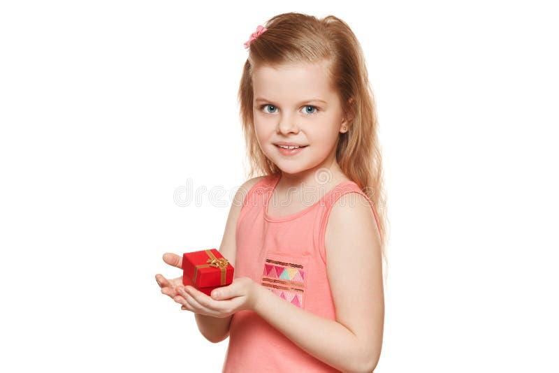 Menina bonito pequena que guarda uma caixa de presente, isolada no fundo branco fotografia de stock