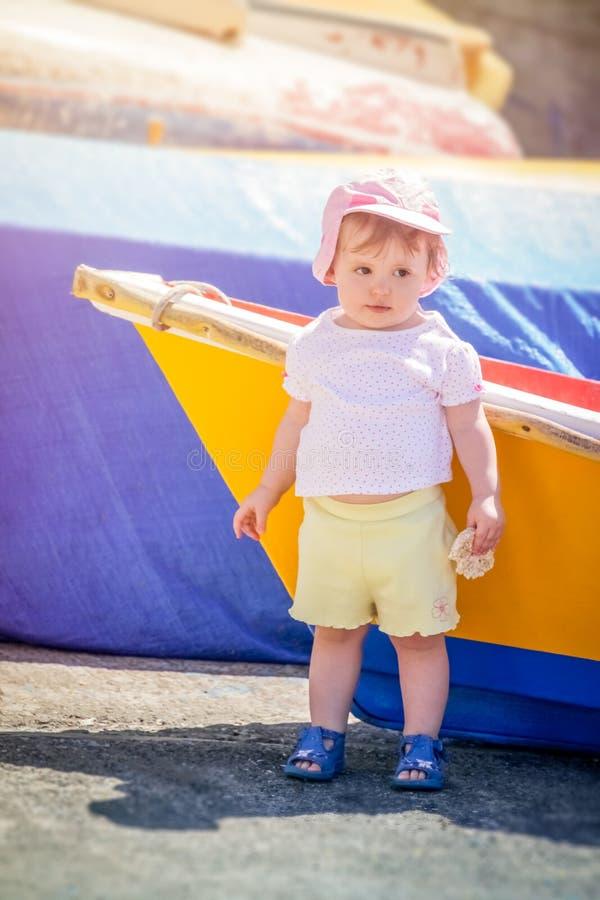 Menina bonito pequena que inclina-se em um barco imagens de stock royalty free