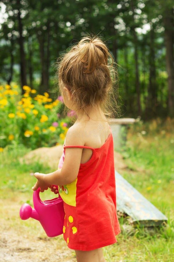 Menina bonito pequena que joga com a lata molhando da planta fotos de stock