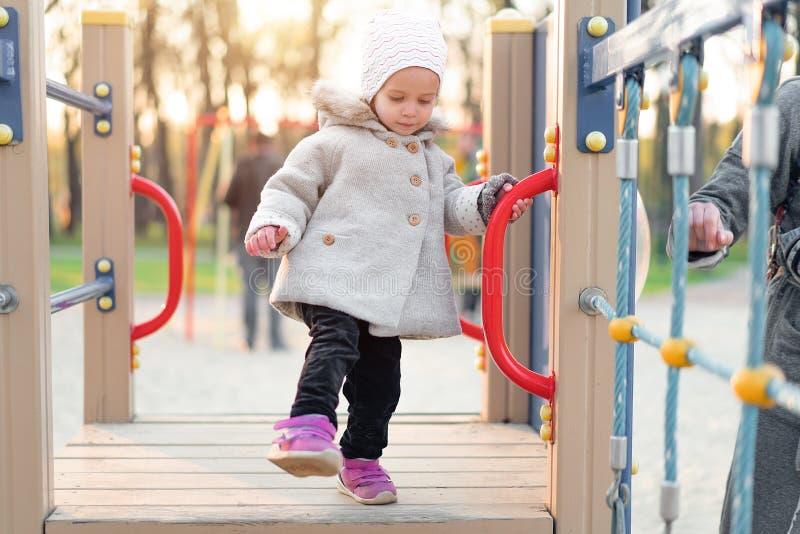 Menina bonito pequena que joga no campo de jogos no outono imagem de stock