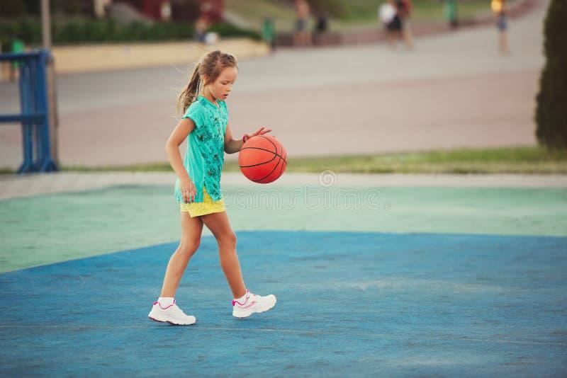 Menina bonito pequena que joga o basquetebol fora imagem de stock