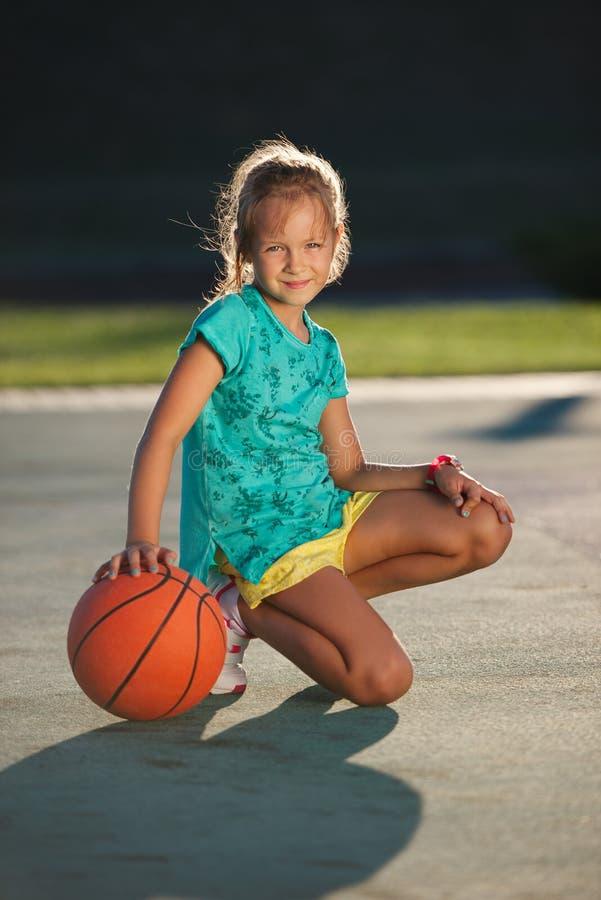 Menina bonito pequena que joga o basquetebol fora fotografia de stock