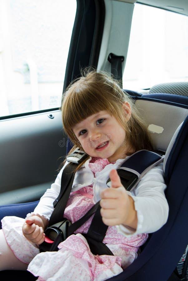 Menina bonito pequena que senta-se no carro no assento da segurança da criança foto de stock royalty free