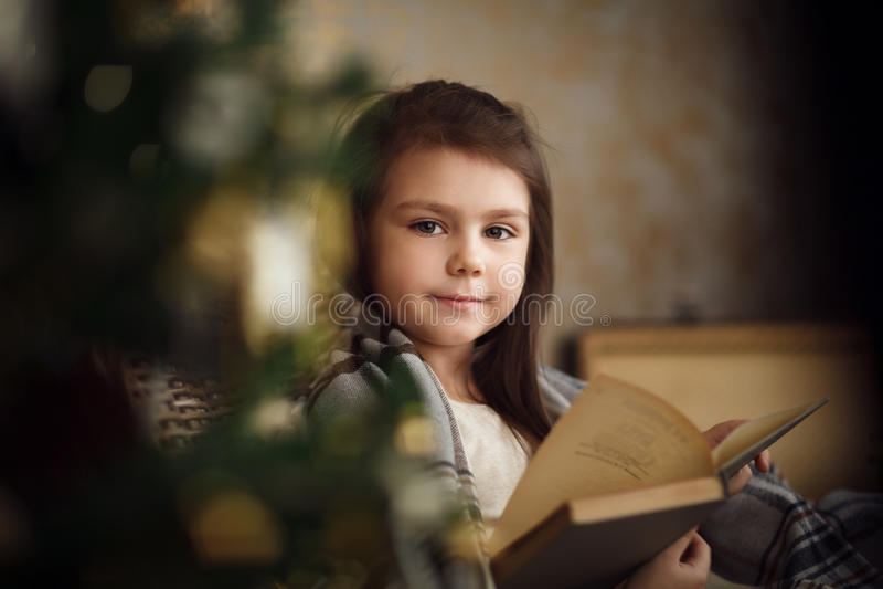 menina bonito pequena que senta-se perto da árvore de Natal e do livro de leitura fotos de stock