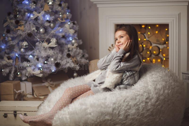 menina bonito pequena que senta-se perto da árvore e da chaminé de Natal imagens de stock royalty free