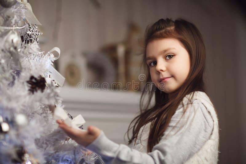menina bonito pequena que senta-se perto da árvore e da chaminé de Natal foto de stock royalty free
