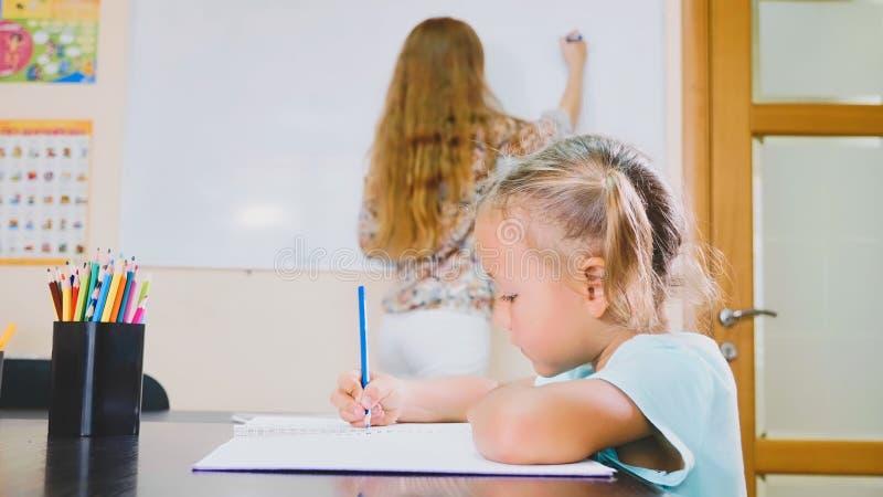 A menina bonito pequena senta-se na sala de aula e estuda-se com o professor no livro de exercício imagens de stock