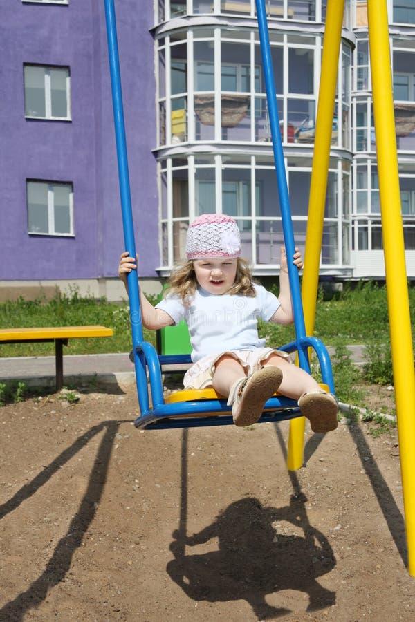 A menina bonito pequena senta-se no balanço fotos de stock royalty free