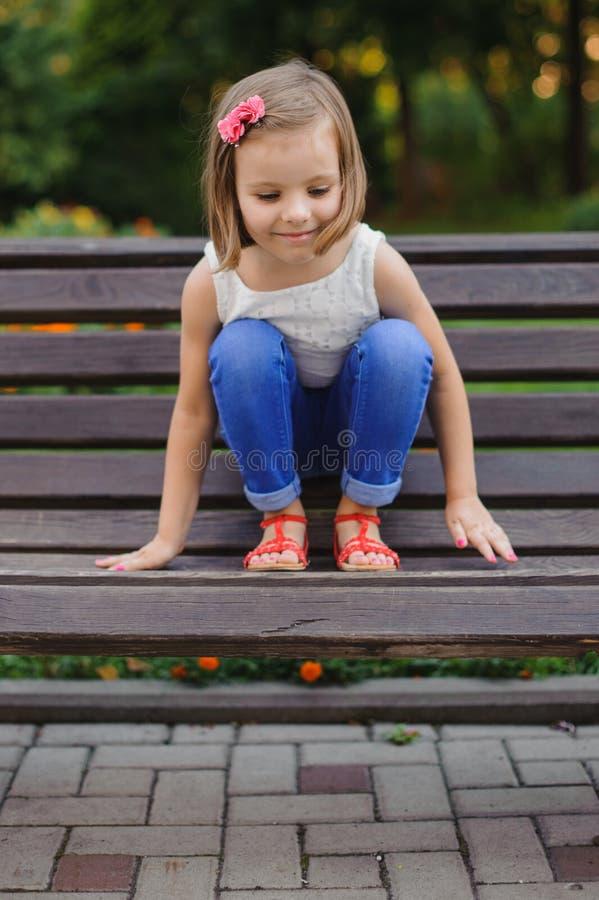 A menina bonito pequena senta-se no banco imagem de stock royalty free