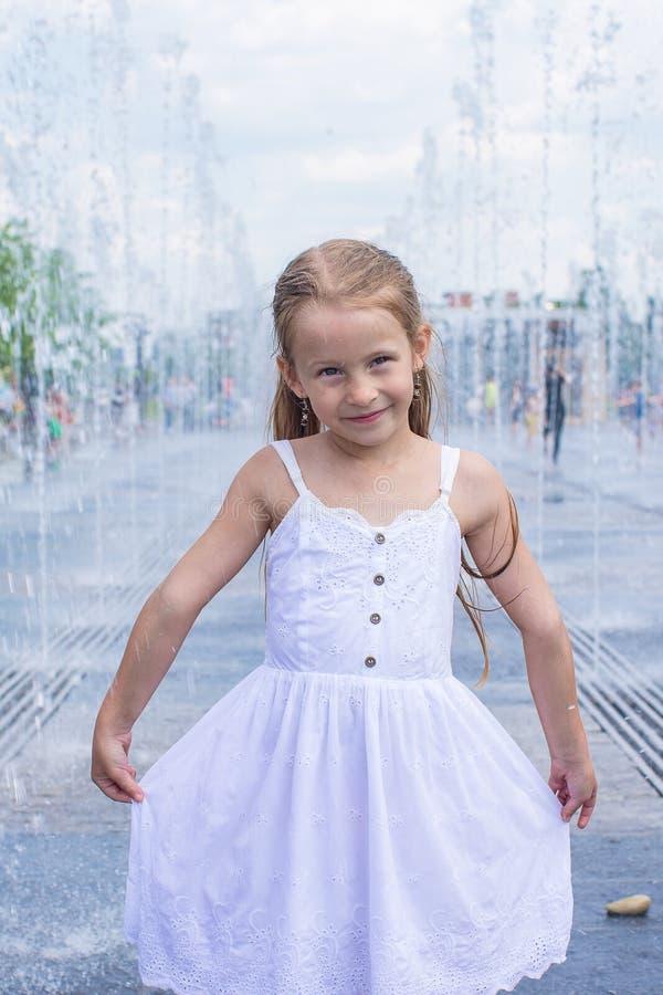 A menina bonito pequena tem o divertimento na fonte aberta da rua imagens de stock royalty free