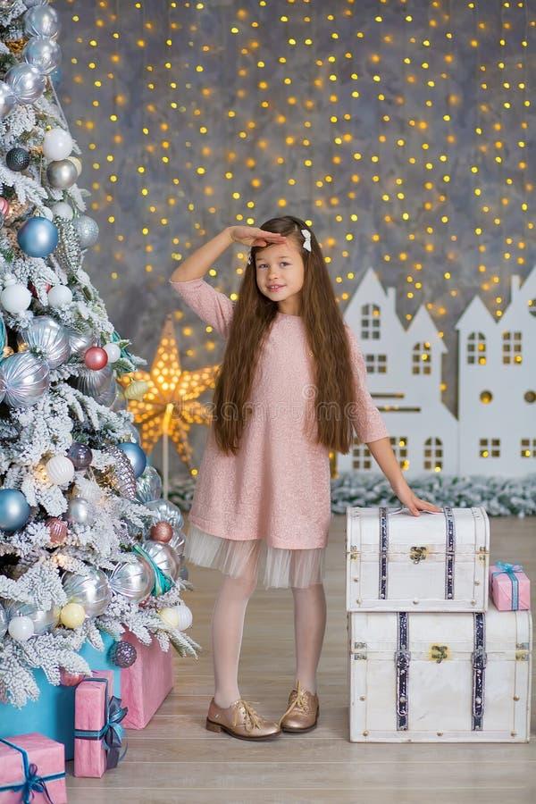 Menina bonito perto da árvore de Natal para apreciar o tempo de inverno do milagre Conceito do Natal Opinião nos milagre fotos de stock royalty free