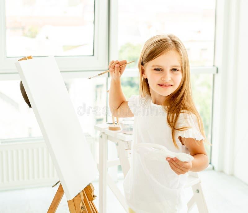 A menina bonito pinta na lona fotografia de stock royalty free