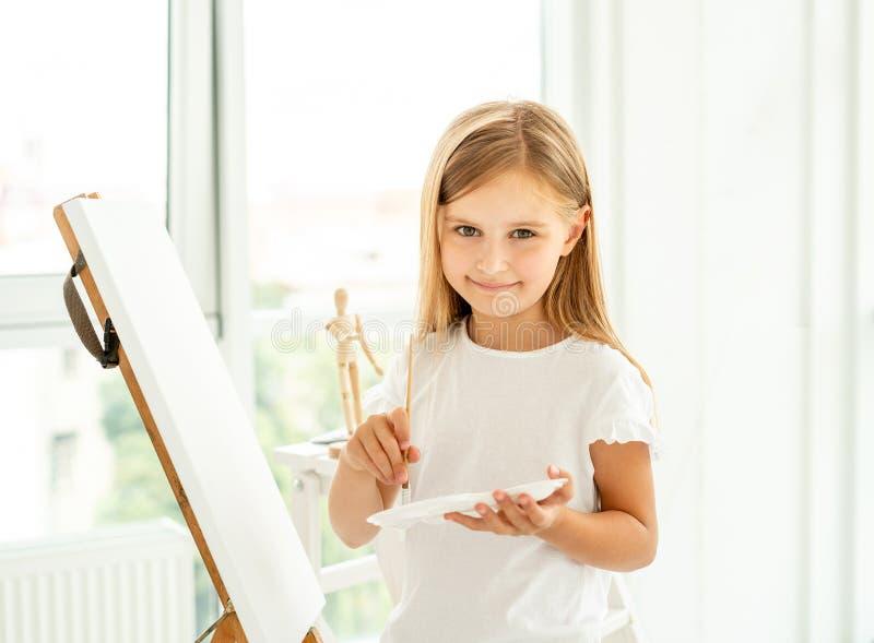 A menina bonito pinta na lona imagem de stock royalty free