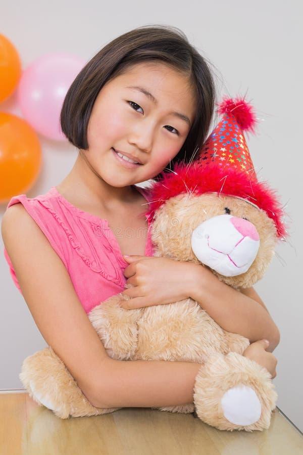 Menina bonito que abraça o brinquedo macio em uma festa de anos fotografia de stock royalty free