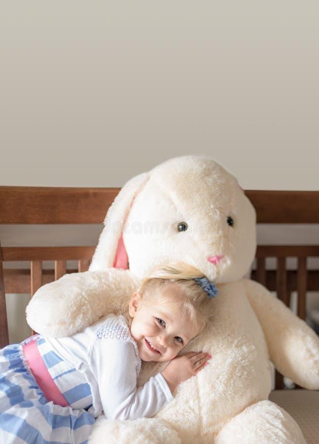 Menina bonito que abraça o coelho enchido imagens de stock royalty free