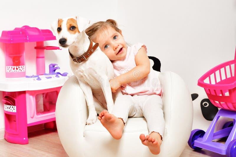 Menina bonito que abraça seu cão foto de stock