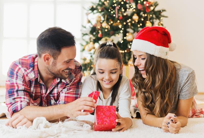 Menina bonito que abre um presente em uma manhã de Natal com sua família fotografia de stock