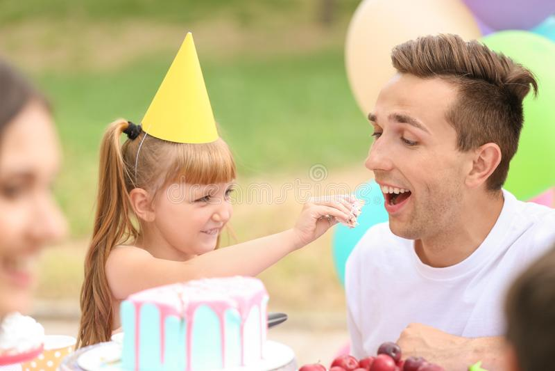 Menina bonito que alimenta seu pai com o bolo na festa de anos fora fotos de stock