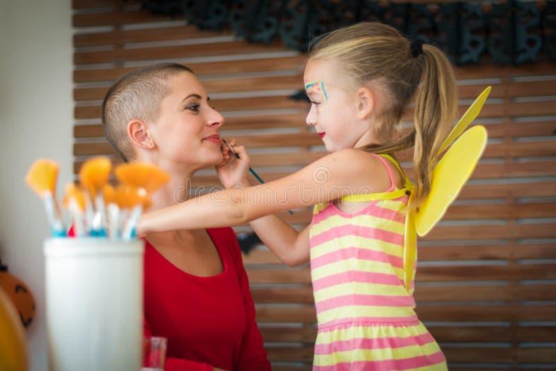 Menina bonito que aplica a pintura da cara a sua cara das mães para o partido de Dia das Bruxas Dia das Bruxas ou fundo do estilo fotografia de stock