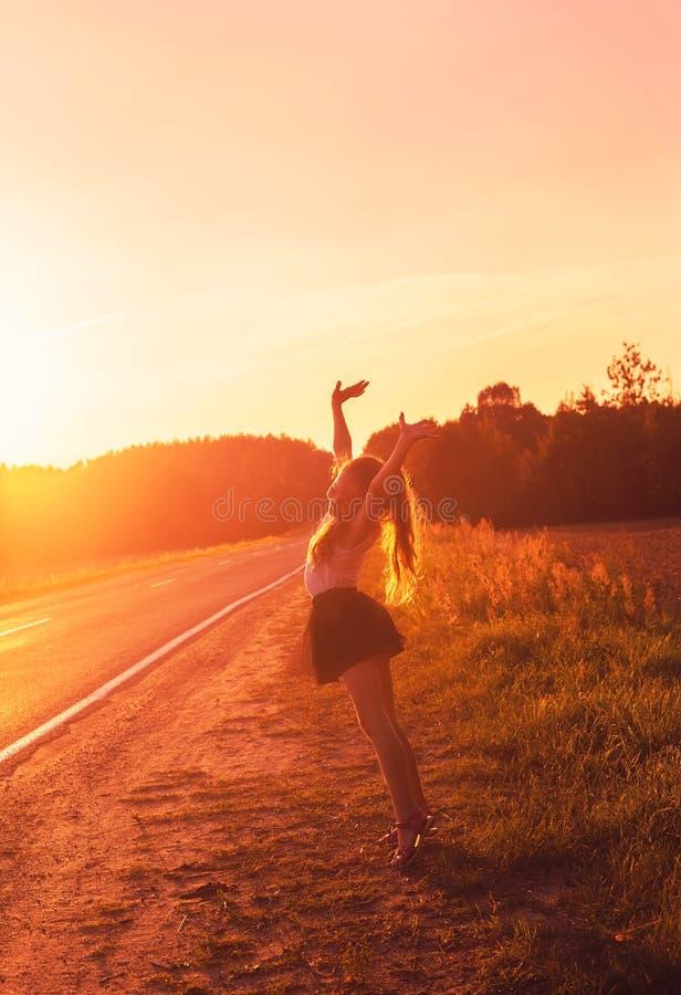 Menina bonito que aprecia fora a viagem por estrada no por do sol Teena bonito foto de stock royalty free