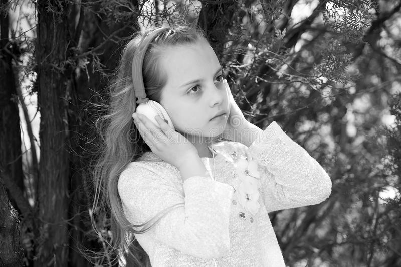 Menina bonito que aprecia a música usando auscultadores imagens de stock royalty free