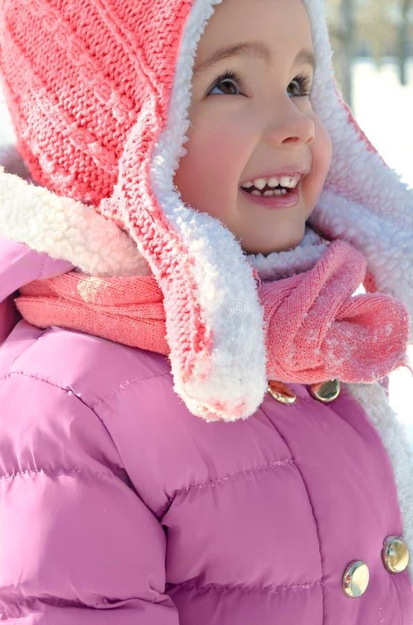 A menina bonito que aprecia o inverno e a neve vestiu-se em brilhante morno imagem de stock