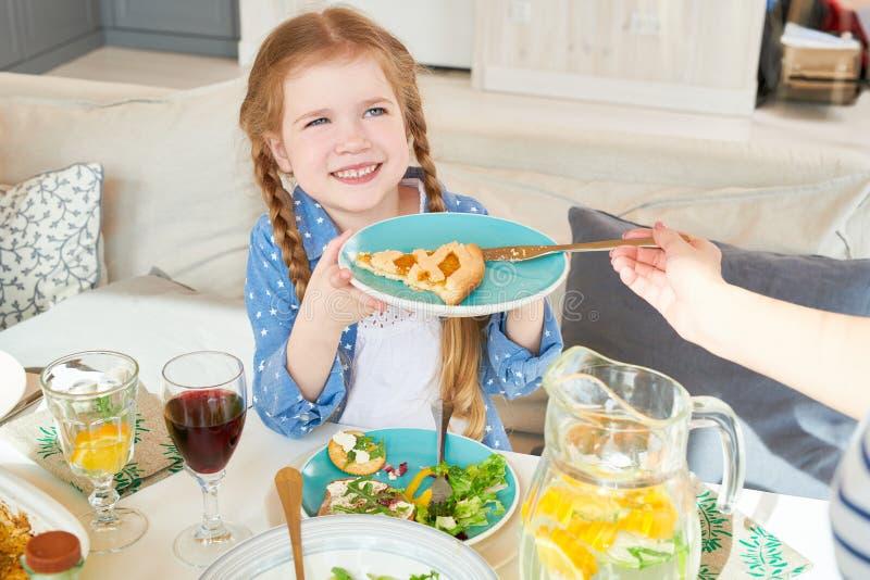 Menina bonito que aprecia o jantar da família imagens de stock