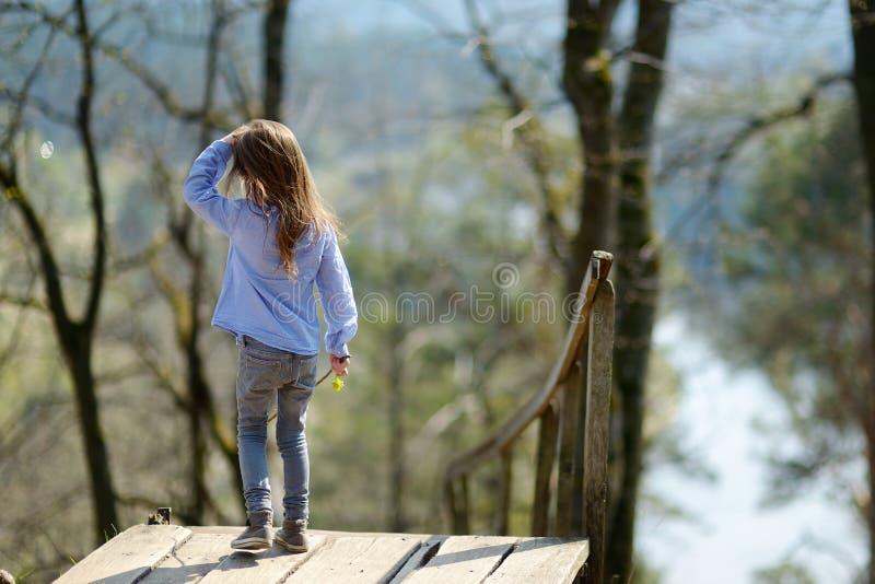 Menina bonito que aprecia uma vista em um rio imagem de stock