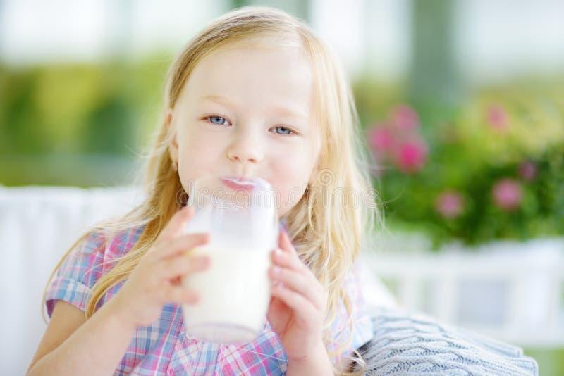 Menina bonito que bebe o leite orgânico fresco no dia de verão ensolarado imagem de stock