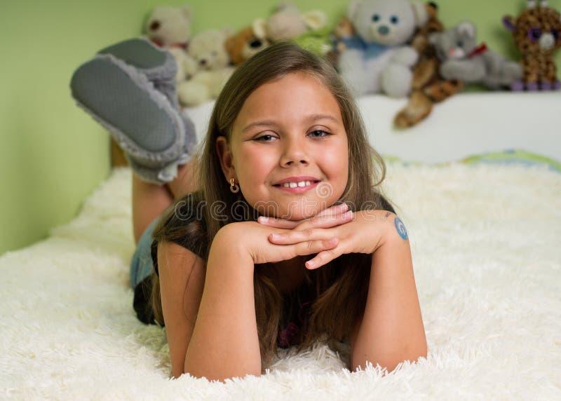 Menina bonito que coloca na cama foto de stock