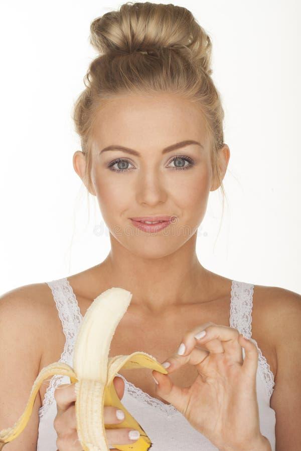 Menina bonito que come a banana imagem de stock royalty free