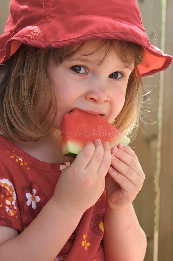 Menina que come o melão fotos de stock